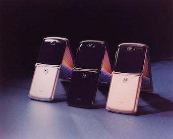 Three Motorola Razrs propped up.