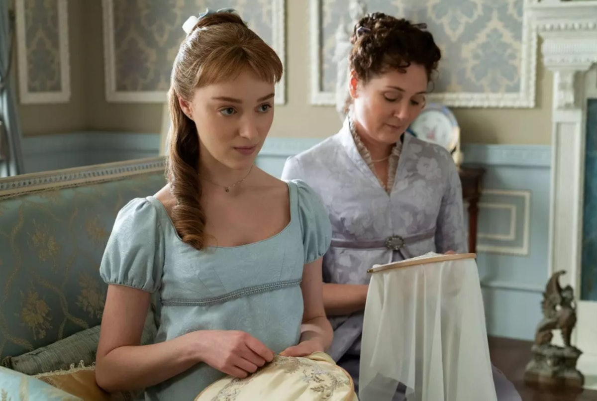 Daphne and her mom embroider on a lavish couch in their drawing room in 'Bridgerton.'