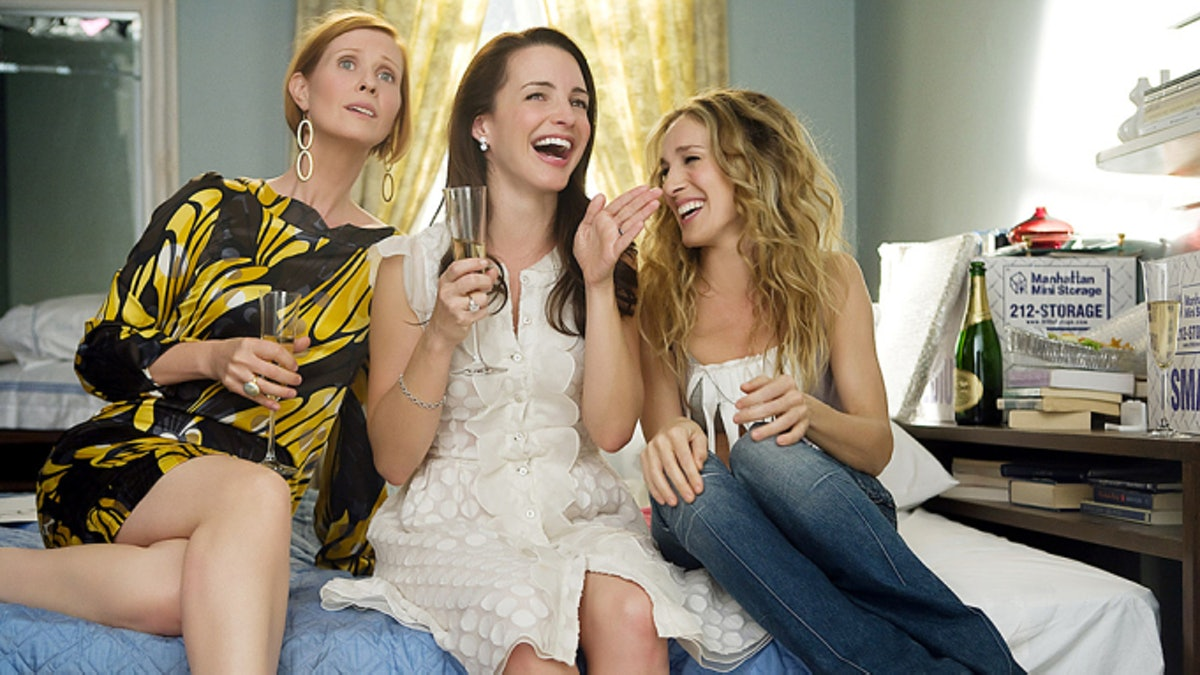Miranda, Charlotte, and Carrie from 'Sex and the City' laugh and drink wine while sitting on a bed.