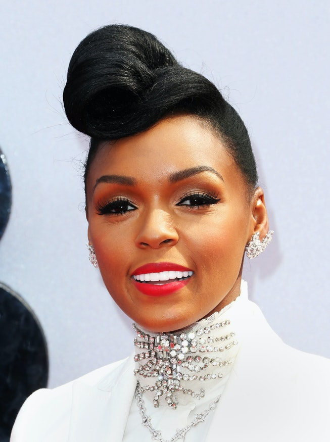 Janelle Monáe wearing red lipstick and a bouffant updo.