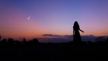 Young woman looking up at crescent moon