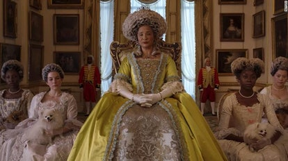 Queen Charlotte from 'Bridgerton' wears a yellow ballgown while sitting in front of her ladies.