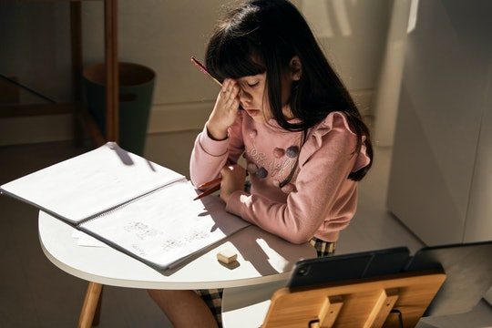 Girl with long brown hair sits at a small table with a notebook, looking tired