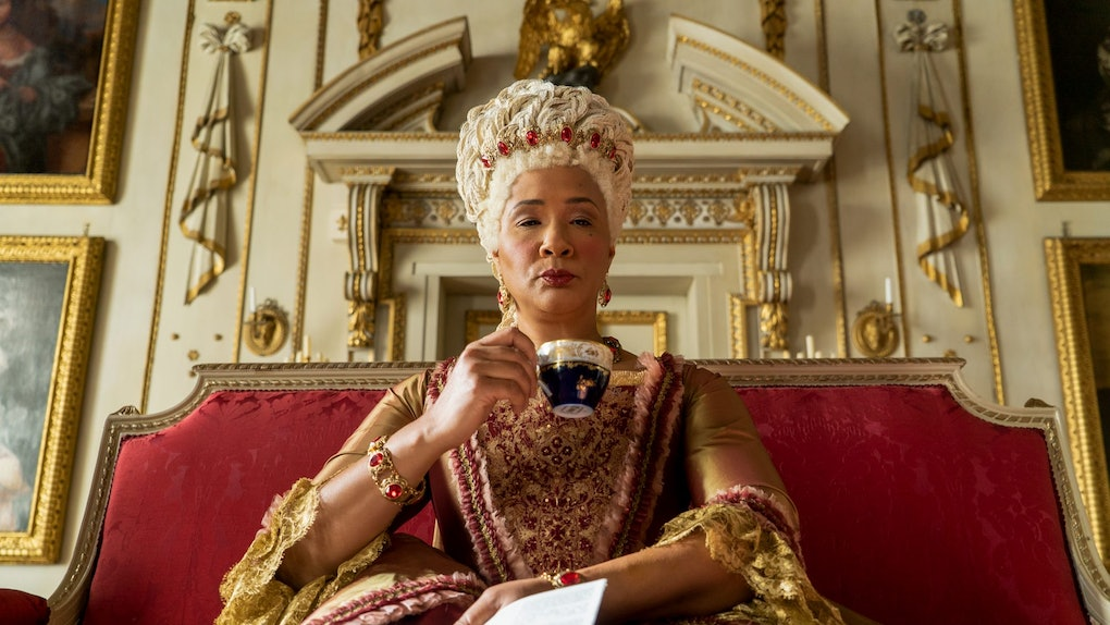 Queen Charlotte from 'Bridgerton' sips tea and holds Lady Whistledown's paper while sitting on a throne.