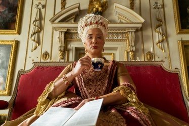 Queen Charlotte from 'Bridgerton' sips tea and holds Lady Whistledown's paper while sitting on a thr...