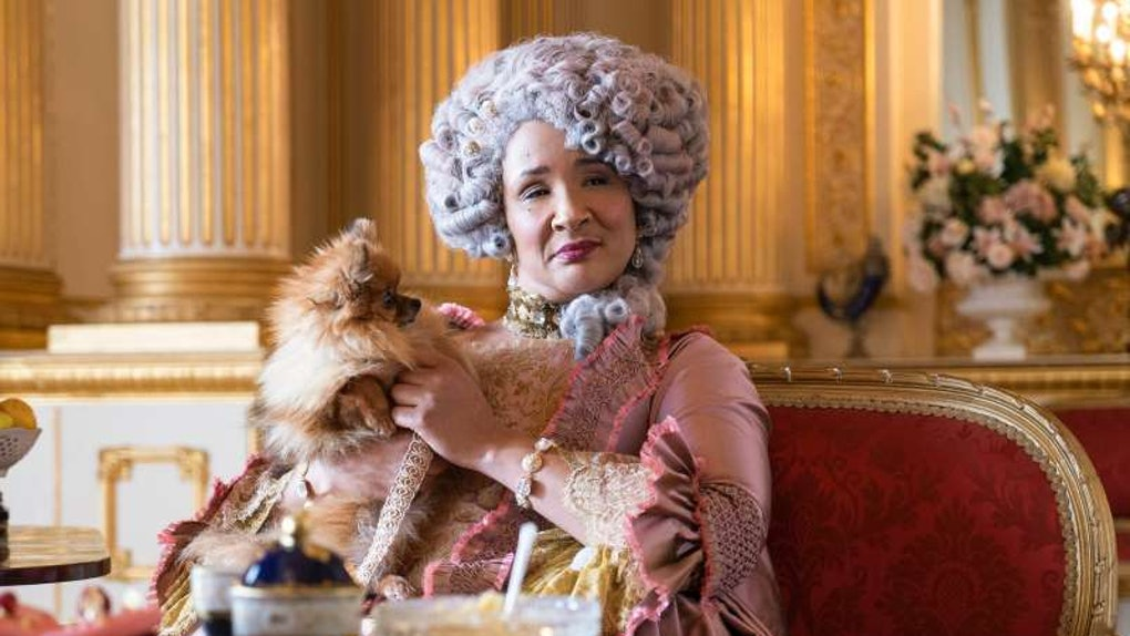 Queen Charlotte from 'Bridgerton' holds her dog and sits in a regal chair while enjoying afternoon tea.