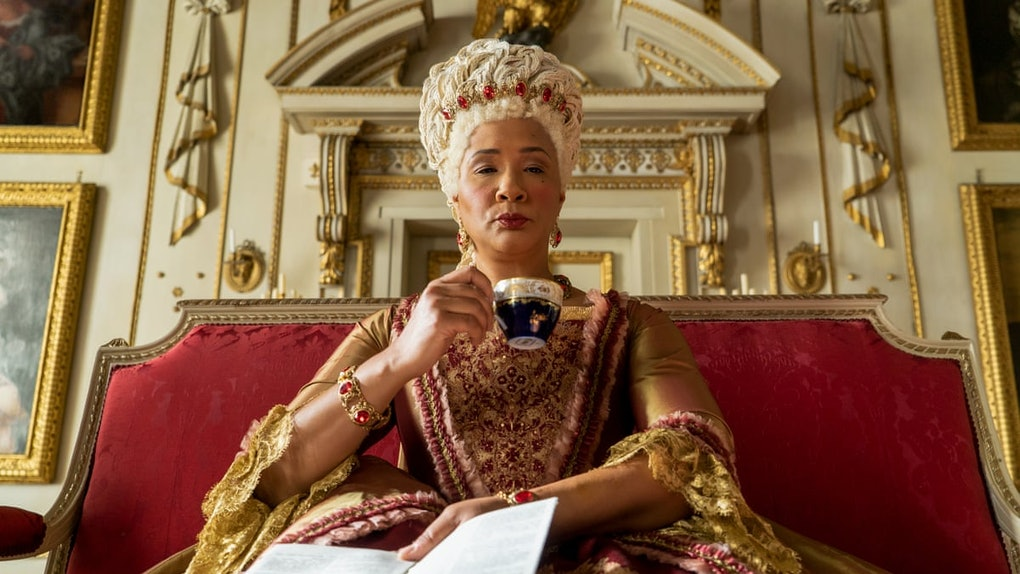 Queen Charlotte sips a cup of tea while sitting on her throne in 'Bridgerton.'
