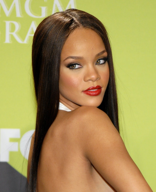 Rihanna strikes a pose on the red carpet, wearing red lipstick and straight brown hair