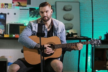 A musician holds a guitar while wearing Finalace headphones in front of a smartphone on a tripod