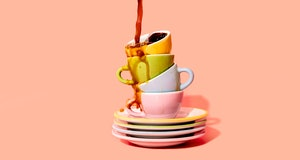Coffee pouring on stack of plates and coffee cups.
