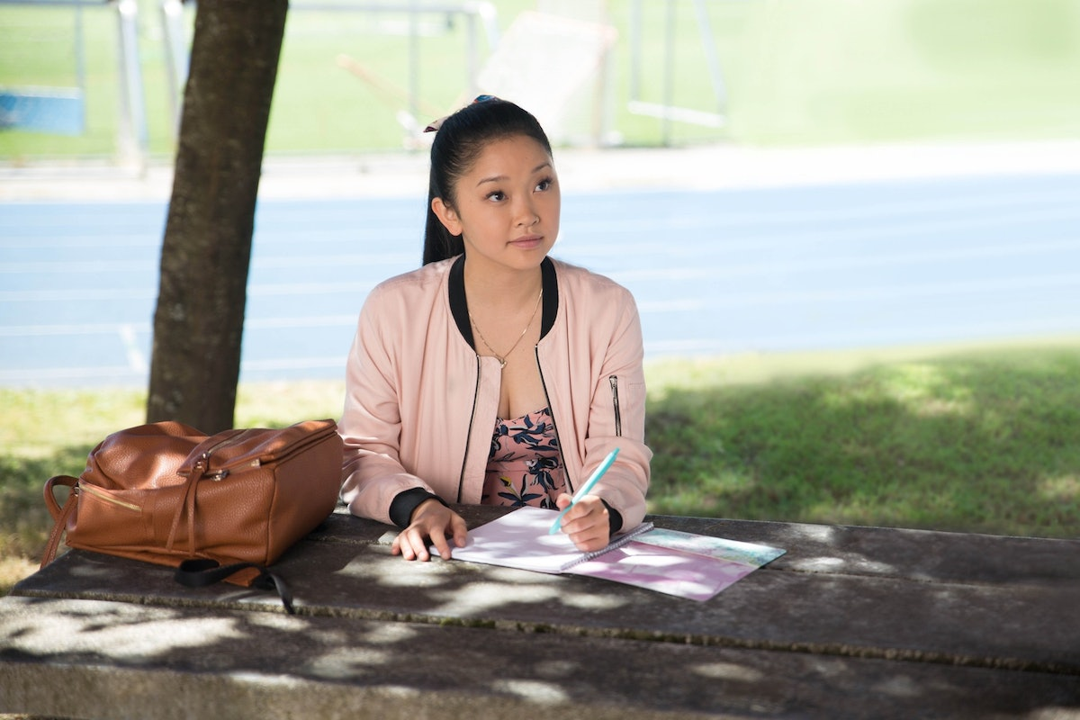 Lara Jean from 'To All The Boys I've Love Before' writes a contract on a picnic table outside.