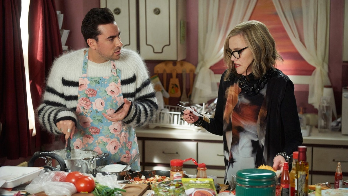 David Rose and Moira fold in the cheese of their enchiladas in the kitchen on 'Schitt's Creek.'