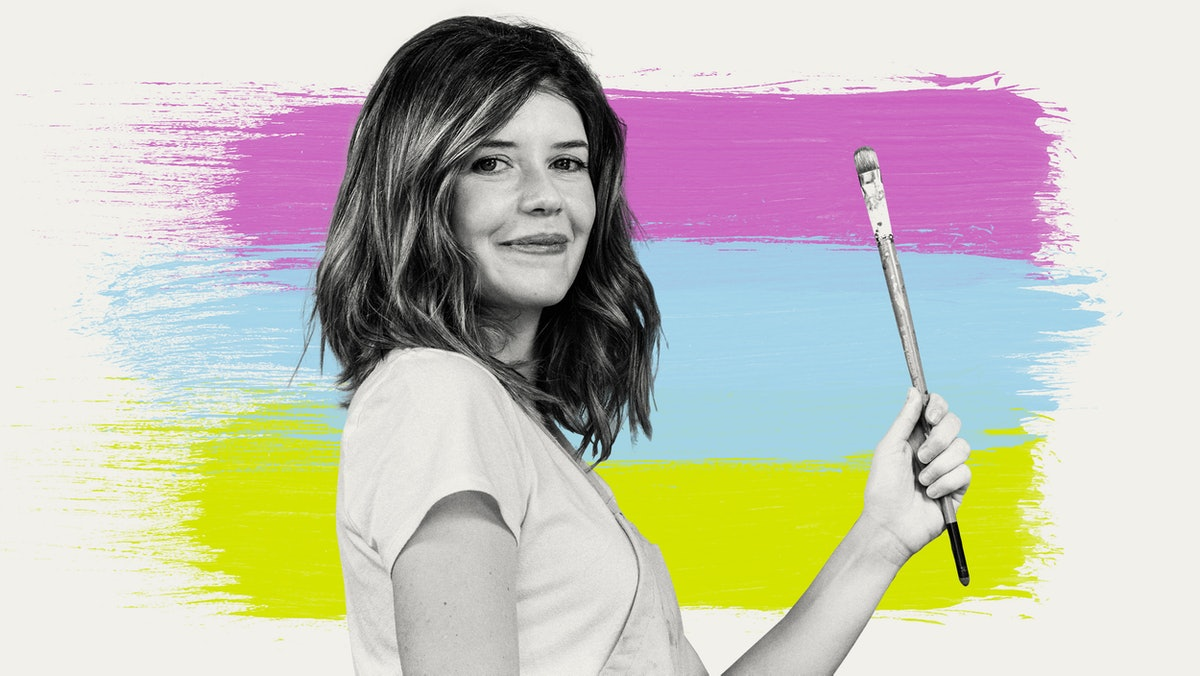 Artist Lourdes Villagomez stands in profile, holding up a paintbrush against a background of three brushes of color in pink, blue, and green
