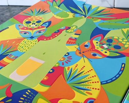 Artwork of two stylized cats, painted in yellow, green, orange, blue, and red, touching paws to sque...