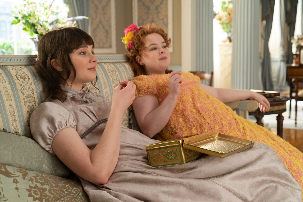 Eloise Bridgerton and Penelope Featherington sit on the couch together in 'Bridgerton.'
