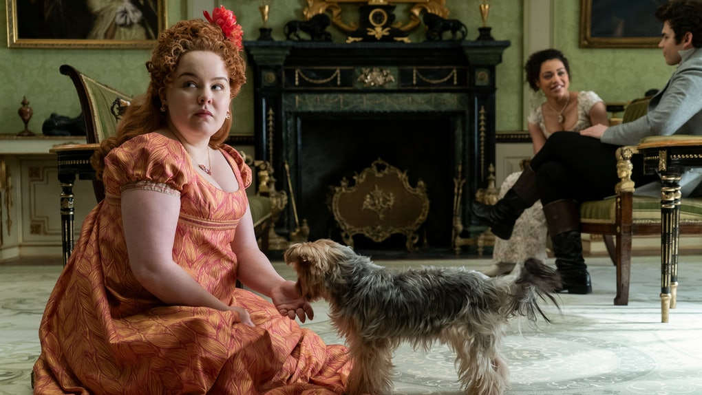 Penelop Featherington from 'Bridgerton' sits on the floor with a dog, while Marina and Colin talk.