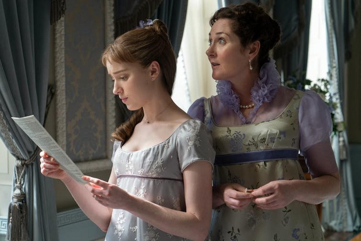 Lady Violet Bridgerton and Daphne Bridgerton stand by the window reading Lady Whistledown's gossip sheet in 'Bridgerton.'