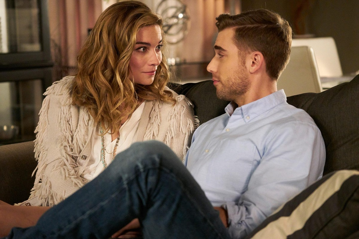 Alexis and Ted from 'Schitt's Creek' look at each other while sitting on a couch.