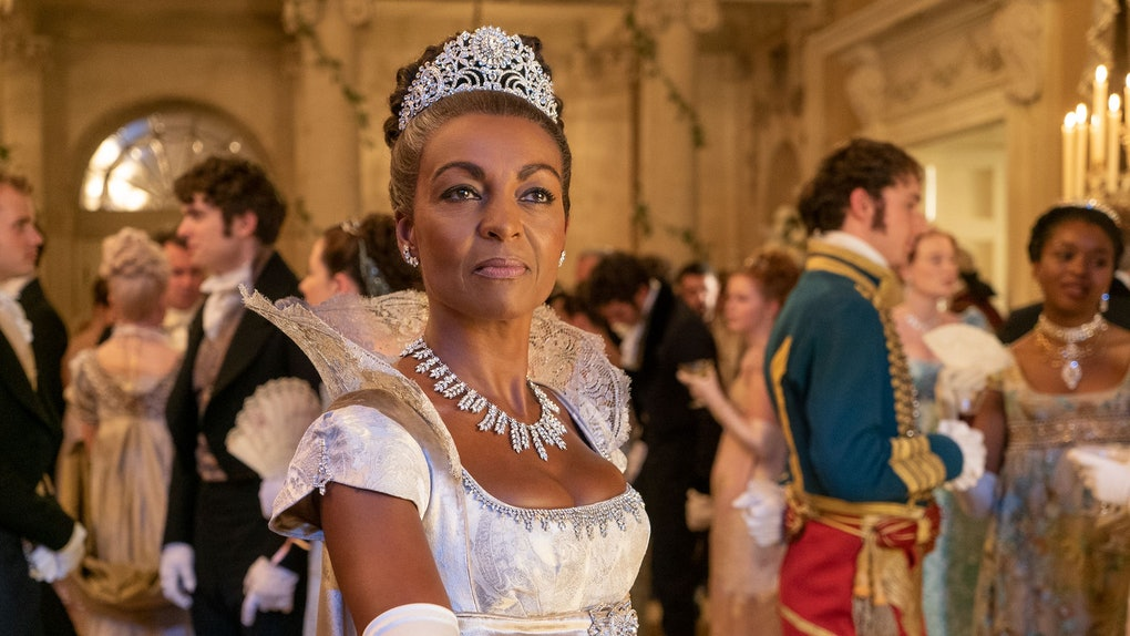 An elegant Lady Danbury stands regally in a ball room, wearing a white dress and tiara.