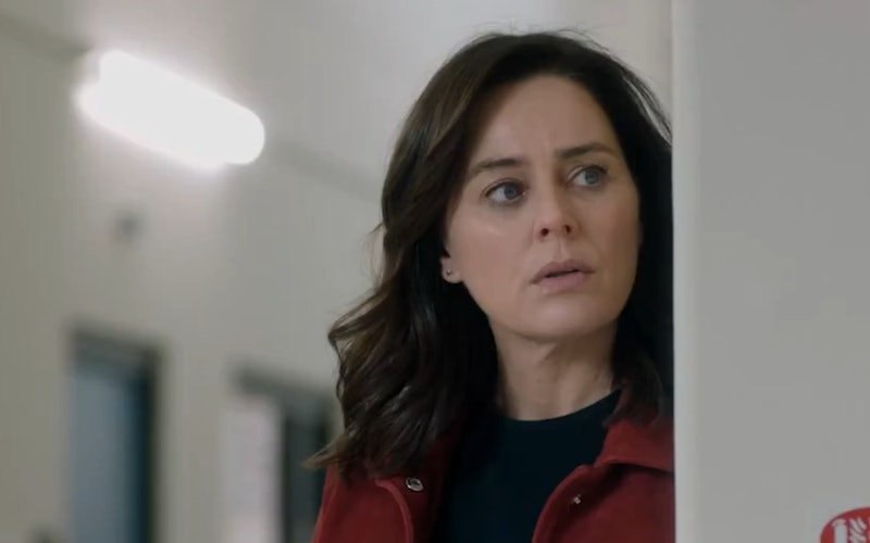 Jill Halfpenny looks round a door suspiciously. She's wearing a red coat and black top
