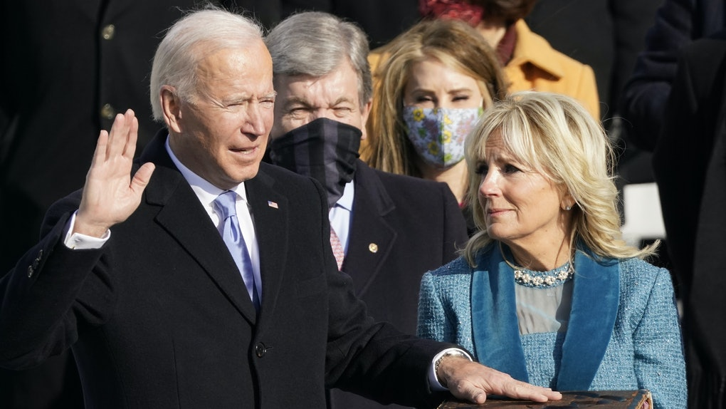 Jill Biden holding up a large Bible while President Joe Biden recites the Presidential Oath.