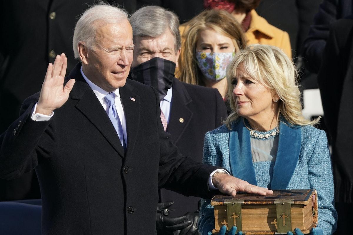 Jill Biden holding up a large Bible while President Joe Biden recites the Presidential Oath.