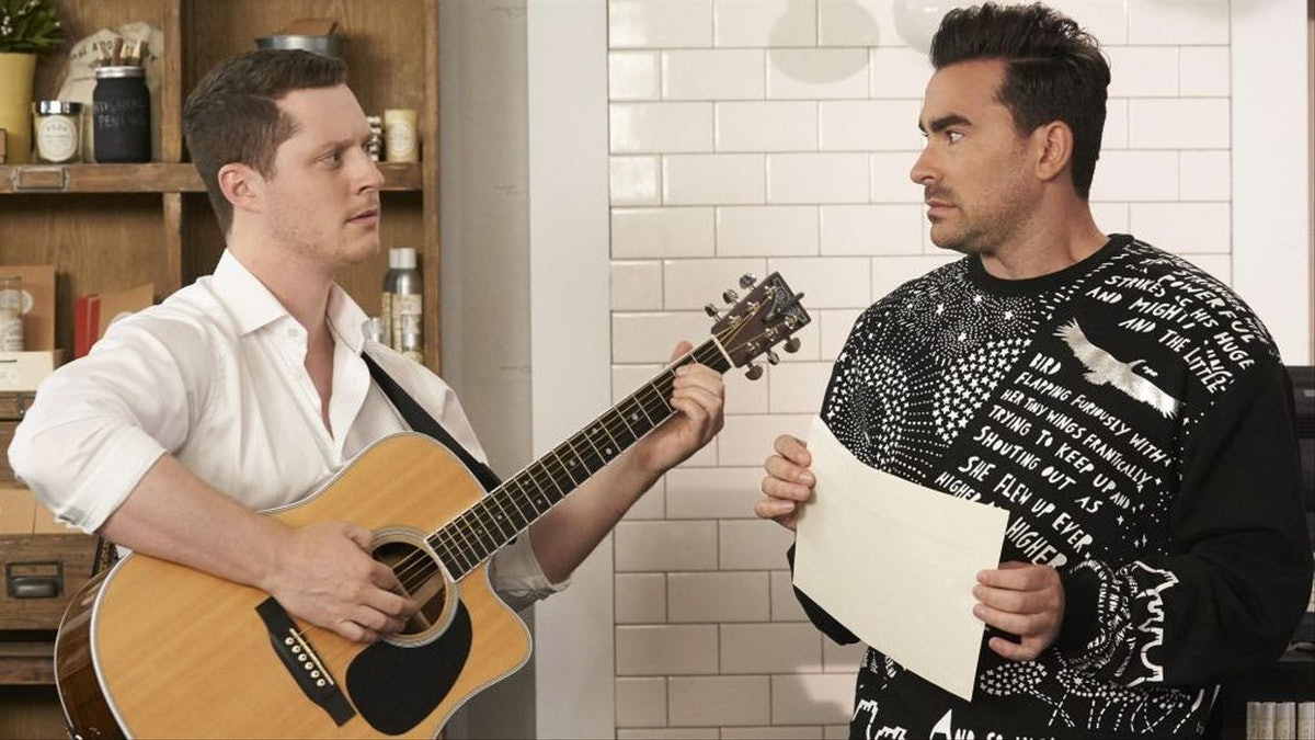 Patrick holds a guitar, while talking to David in Rose Apothecary in 'Schitt's Creek.'