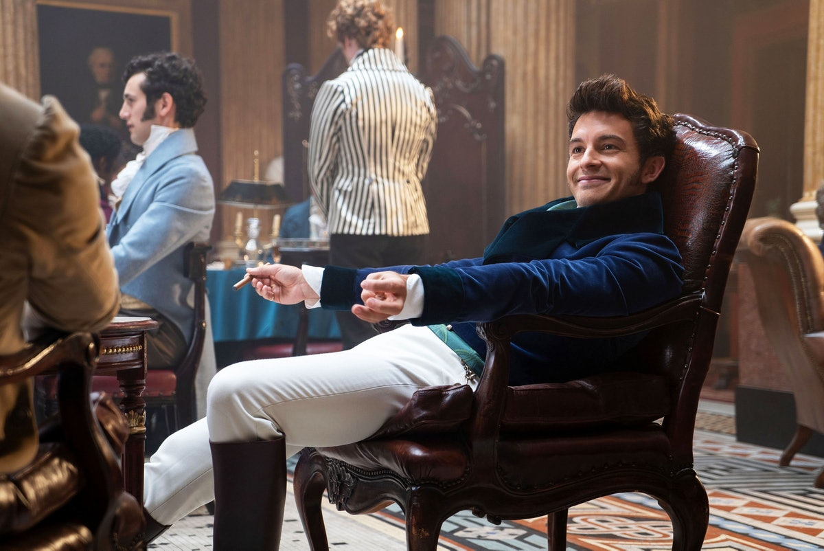Anthony Bridgerton sits in a chair, smiling in 'Bridgerton.'