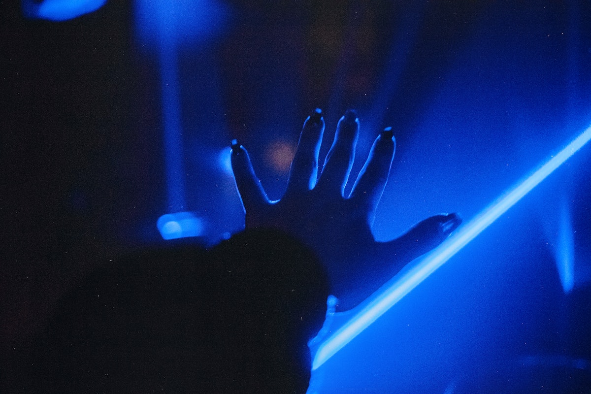 Human Hand On Blue Neon Background