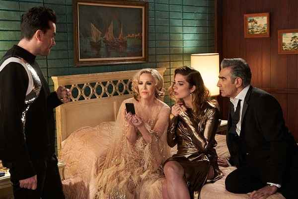 The Rose family from 'Schitt's Creek' looks at a phone in the Schitt's Creek Motel.