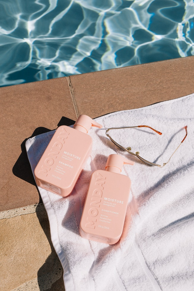 Two pink bottles of MONDAY hair care products on a towel by the pool.