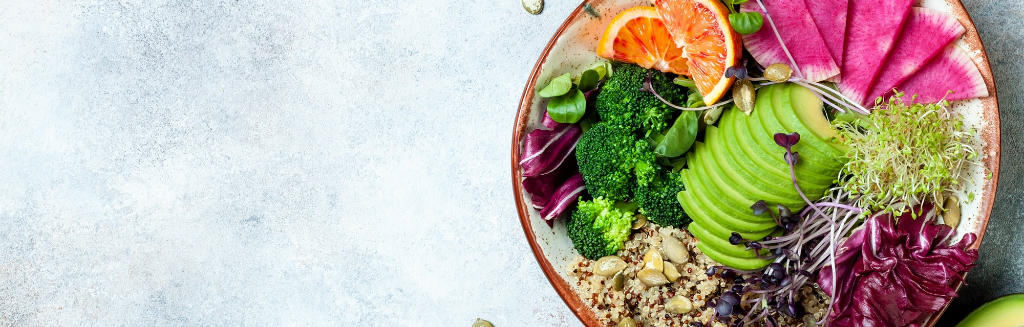 Vegan, detox Buddha bowl with quinoa, micro greens, avocado, blood orange, broccoli, watermelon radish, alfalfa seed sprouts.