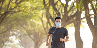 young man in face mask and running in the park