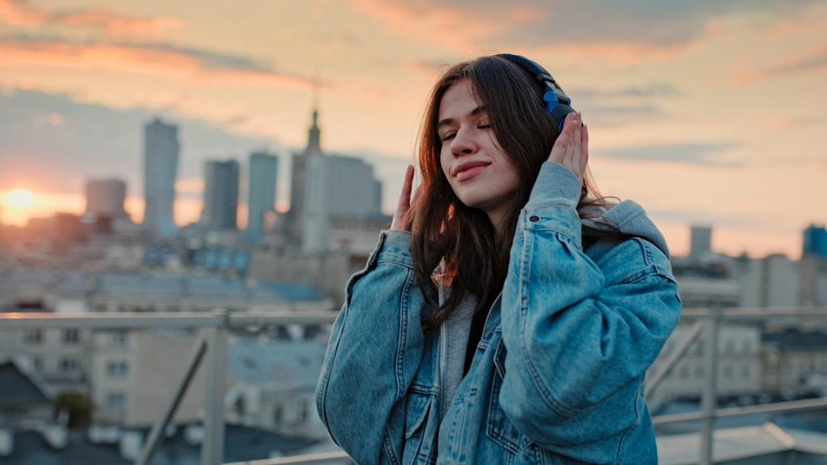 Young woman listening to music via headphones