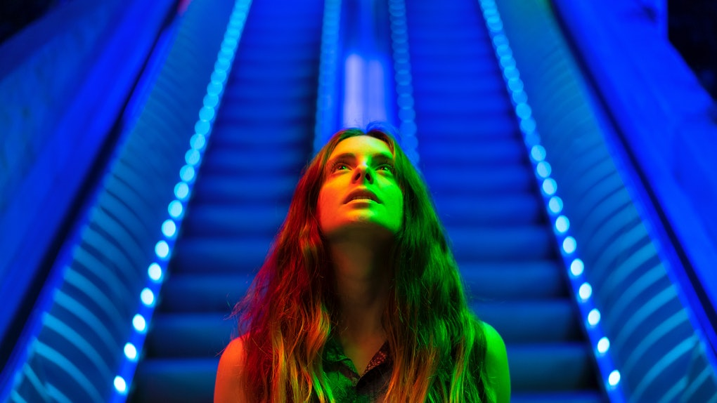 Portrait of illuminated young woman in front of blue lighted escalator looking up