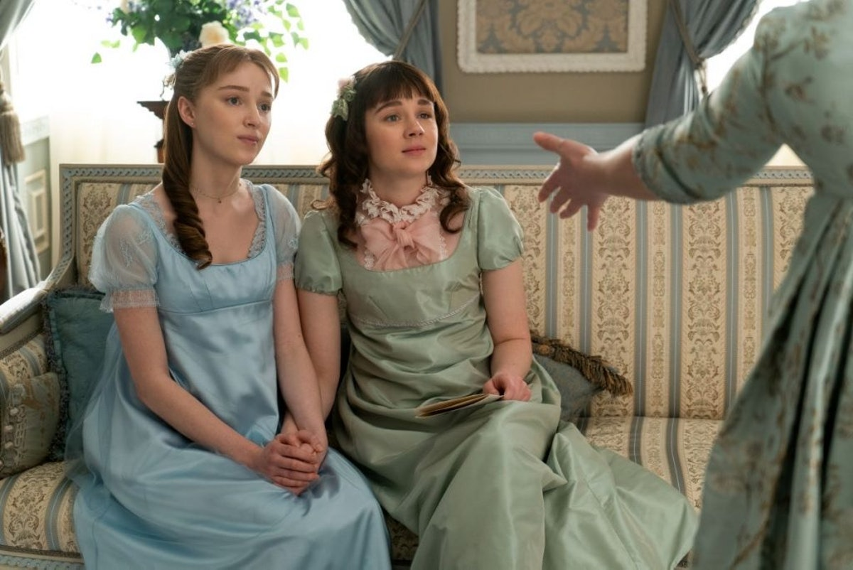 """Eloise and her sister, Daphne, hold hands on the couch in a scene from """"Bridgerton."""""""