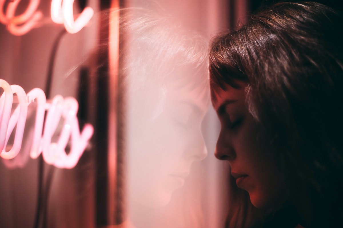 Reflection Of Thoughtful Woman On Window Glass