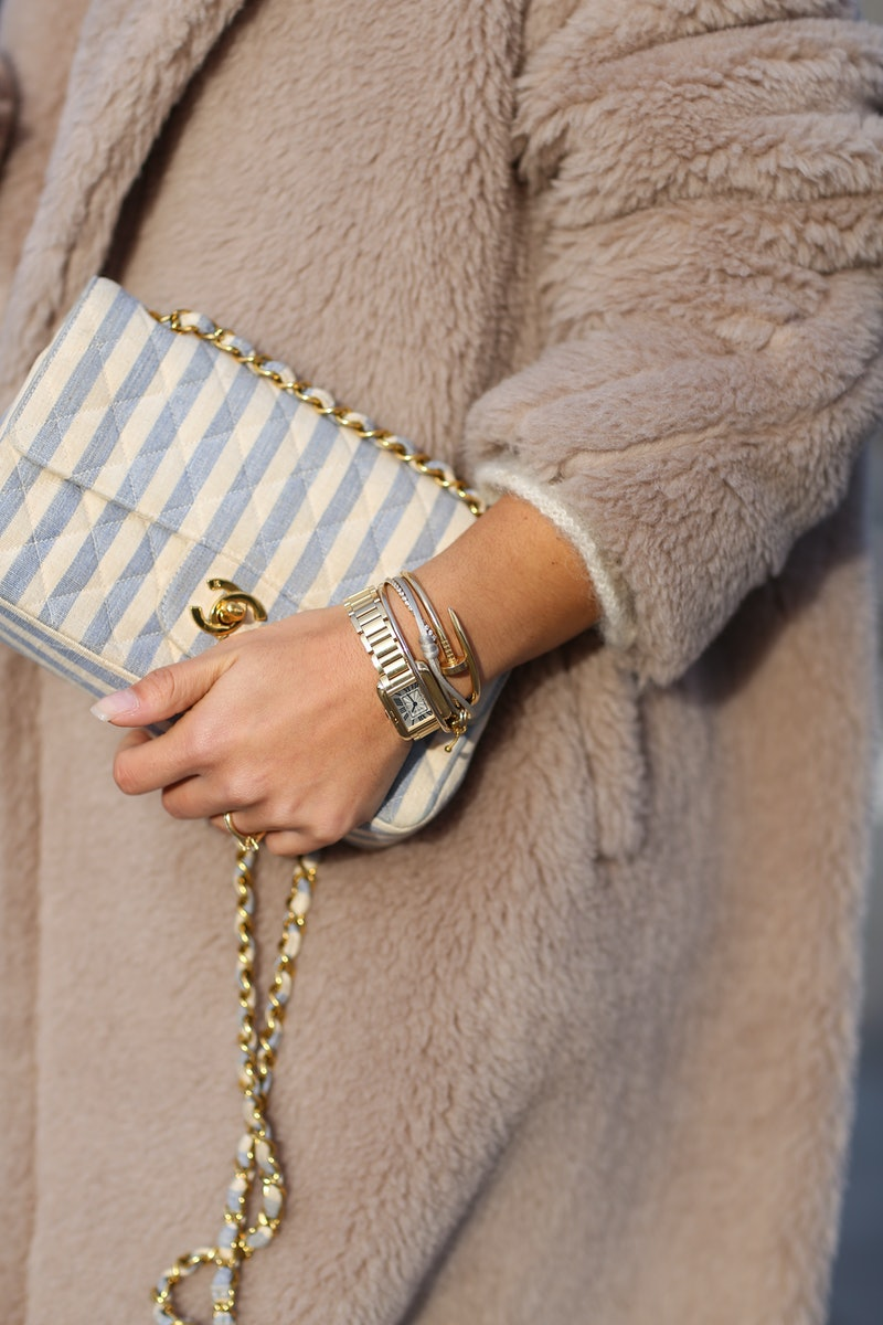 Person wearing a furry coat, holding a Chanel bag and wearing a wristwatch.