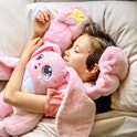 A child lays hugging a pink stuffed animal