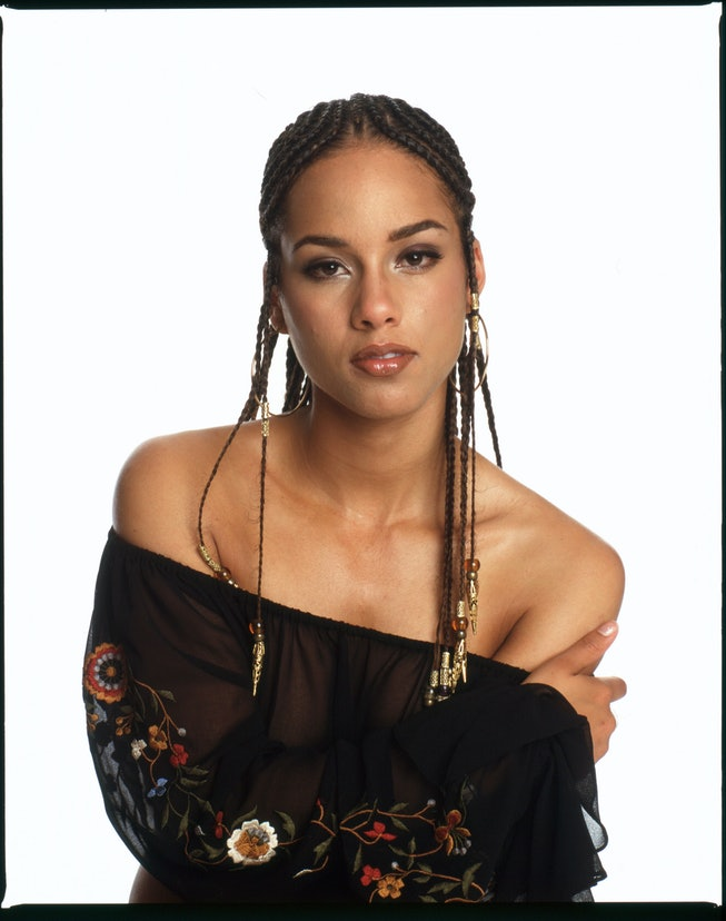 Alicia Keys, her hand on her shoulder, poses in a top, braids hanging down below her shoulders