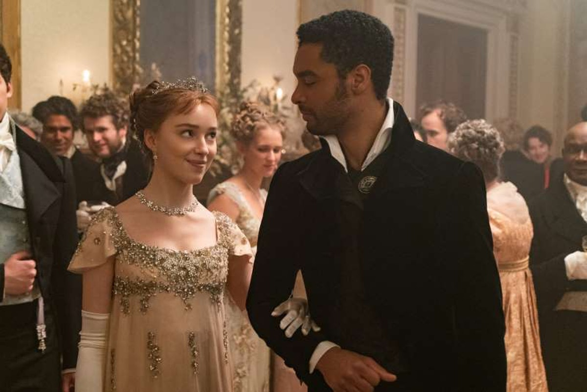 Daphne and Simon walk together through the ball in 'Bridgerton.'