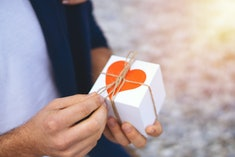 man holding a wrapped valentine's day gift