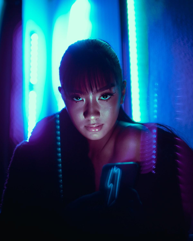 Asian girl staring into the camera in neon futuristic room to represent most greedy zodiac signs