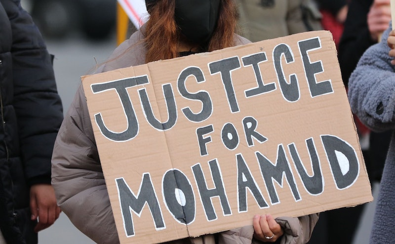 A woman holds a sign at the protest about Mohamud Mohammed Hassan's death in Cardiff, Wales.