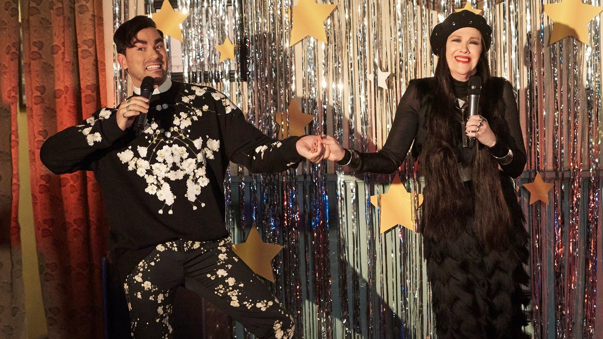 David and Moira Rose sing in front of a silver foil curtain on 'Schitt's Creek.'