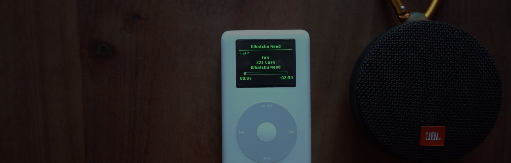 A screenshot of a 17-year-old iPod with Spotify streaming on it. It is placed next to a bluetooth speaker on a wooden desk.
