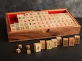 A traditional wooden mahjong set is displayed in a handcrafted wooden box.
