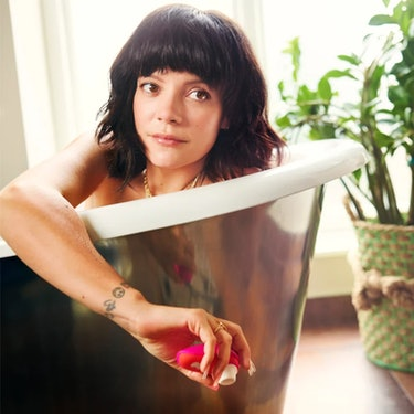 Singer Lily Allen poses in a tub holding a pink and orange Womanizer sex toy