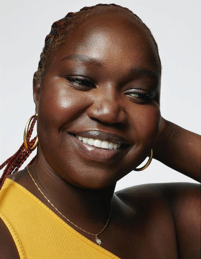 Black model smiling for Milk Makeup ad campaign in yellow shirt and braids.