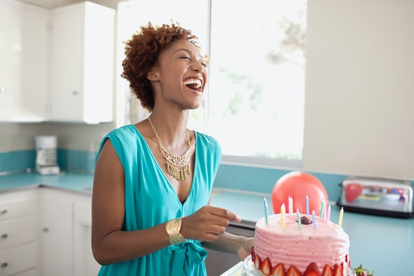 Young woman celebrating birthday with cake
